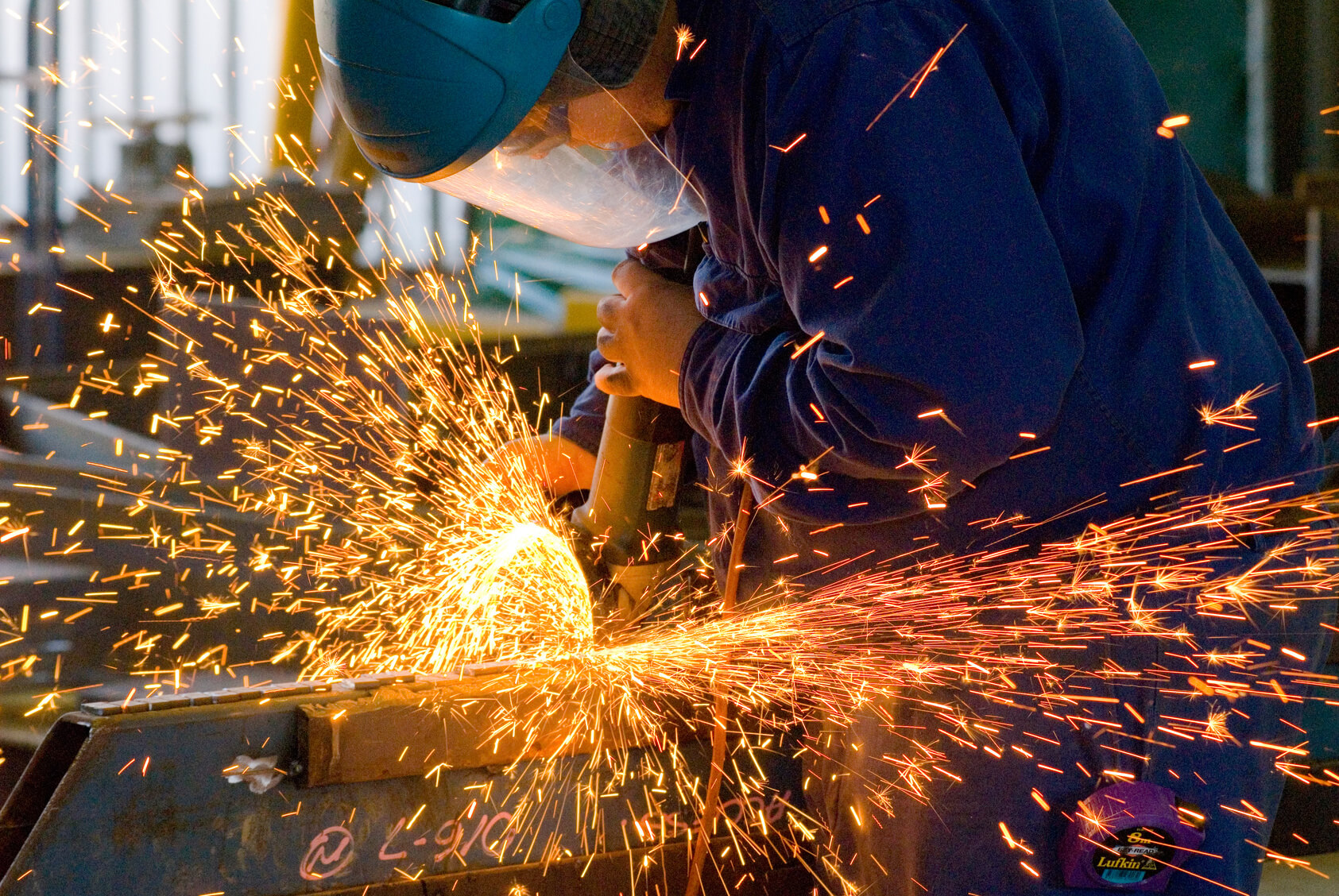 Men at work grinding steel with a grinder in a metal fabrication factory and throwing off bright orange sparks around him while he works